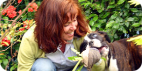 Bild på Yvonne i trädgården med boxer-hunden Samba.